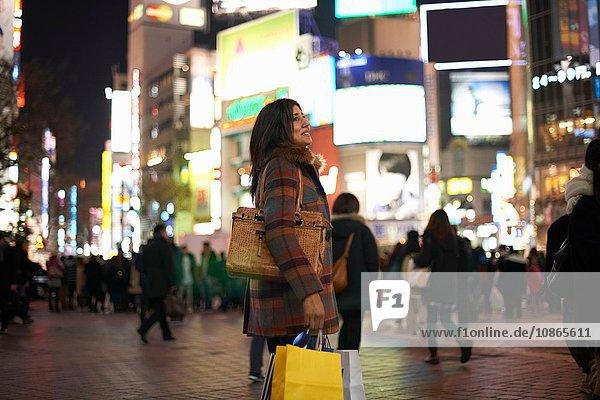 Seitenansicht einer reifen Frau  die nachts in der Stadt Hand- und Einkaufstaschen trägt und lächelnd aufblickt  Shibuya  Tokio  Japan