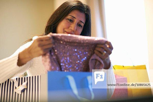 Reife Frau beim Ausziehen von Kleidung aus Einkaufstaschen