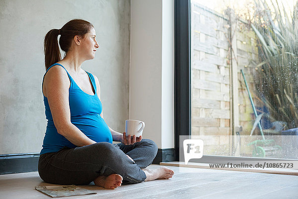 Pregnant woman sitting on floor crossed legged holding coffee cup looking away out of window