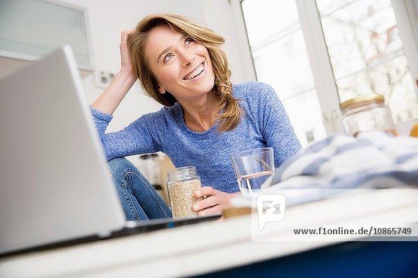 Glückliche Frau sitzt am Küchentisch mit Laptop