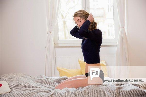 Mittlere erwachsene Frau  die mit den Händen im Haar auf dem Bett kniet