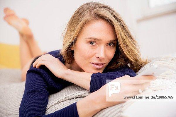 Porträt einer auf dem Bett liegenden Frau mit Smartphone