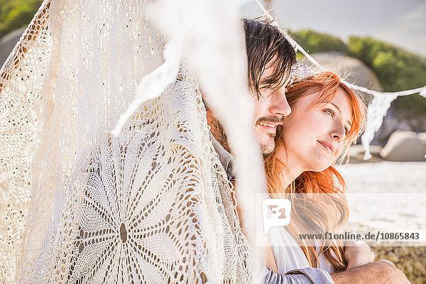 Paar am Strand sitzend im Spitzen Tipi und schaut weg