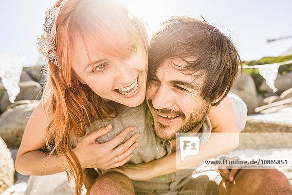 Frau hinter Mann Arme um die Schultern lächelnd