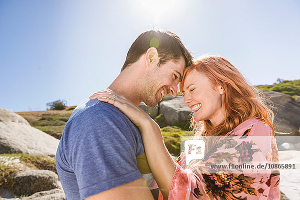 Couple hugging outdoors  face to face  laughing