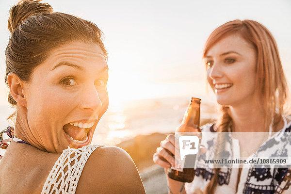 Porträt von zwei Freundinnen im mittleren Erwachsenenalter  die bei Sonnenuntergang am Strand Gesichter ziehen  Kapstadt  Südafrika