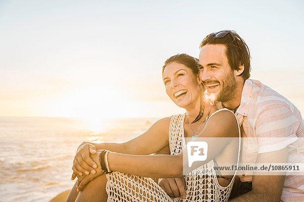 Mittelgroßes erwachsenes Paar sitzt bei Sonnenuntergang am Strand  Kapstadt  Südafrika