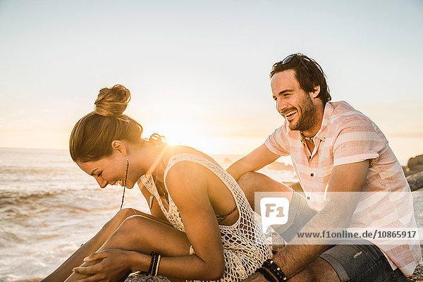 Mittelgroßes erwachsenes Paar  das bei Sonnenuntergang am Strand lacht  Kapstadt  Südafrika