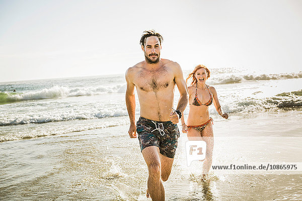 Mid adult couple wearing bikini and swimming shorts running in sea  Cape Town  South Africa