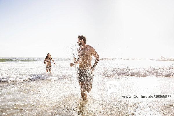 Mittelgroßes erwachsenes Paar in Badeshorts im Meer laufend  Kapstadt  Südafrika