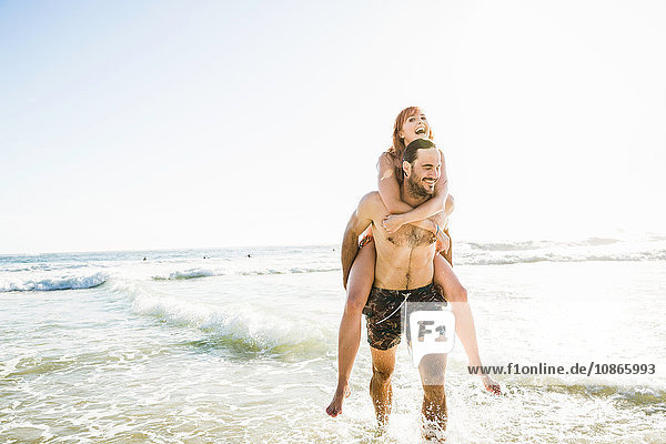 Mann in Badeshorts gibt seiner Freundin Huckepack ins Meer  Kapstadt  Südafrika