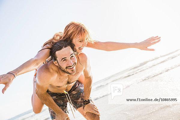 Mittelgroßer erwachsener Mann gibt Freundin Huckepack am Strand  Kapstadt  Südafrika