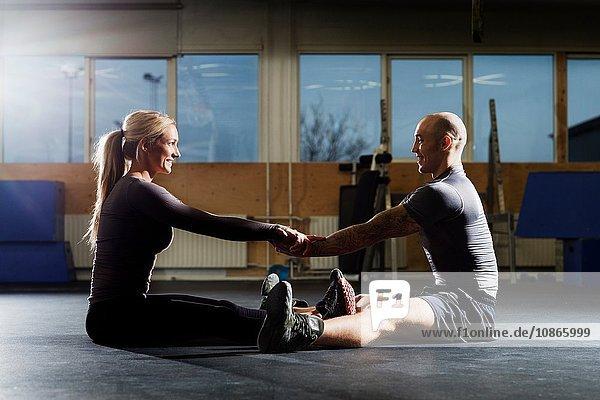 Männliche und weibliche Crossfitter trainieren gemeinsam auf dem Turnboden