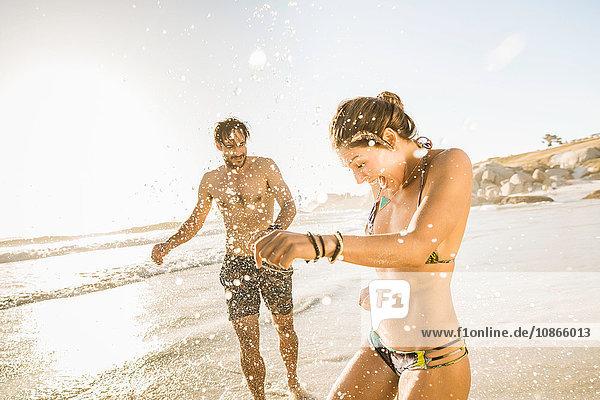 Mittelgroßes erwachsenes Paar in Bikini und Shorts am Strand planschend  Kapstadt  Südafrika