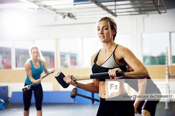 Weibliche und männliche Crossfitter trainieren mit Vorschlaghammer im Fitnessstudio