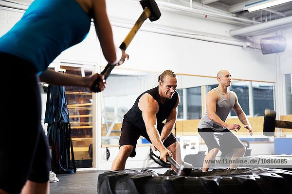 Female and male crossfitters training with sledgehammers on tyres in gym