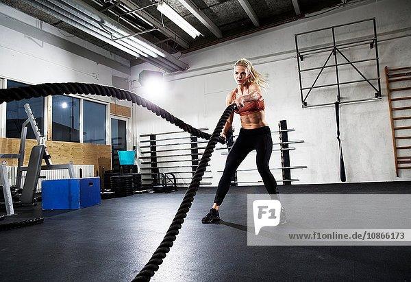 Mittleres Crossfitter-Training für erwachsene Frauen mit Kampfseilen in der Turnhalle