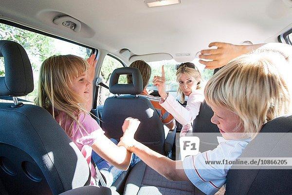 Kämpfende Kinder auf dem Rücksitz eines Fahrzeugs bei einer Autofahrt