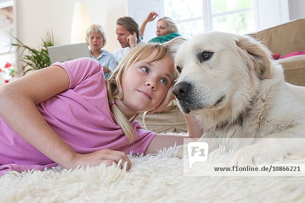 Girl and pet dog lying on carpet  family using laptop in background