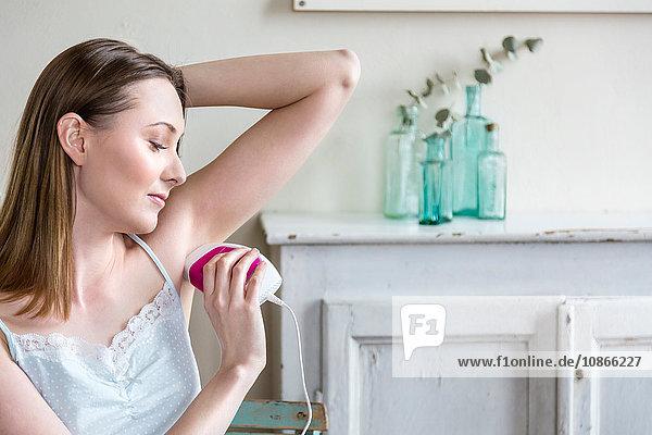 Frau rasiert sich die Achselhöhle mit dem Elektrorasierer
