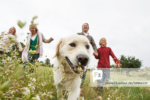 Happy family running with pet dog in park