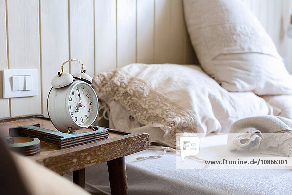 Unmade bed  alarm clock on bedside table