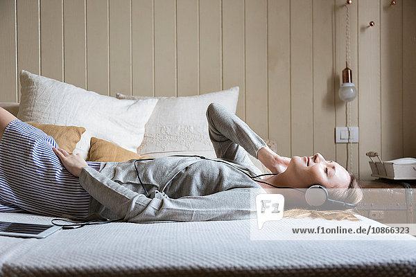 Auf dem Bett liegende Frau mit Kopfhörern  Augen geschlossen und lächelnd