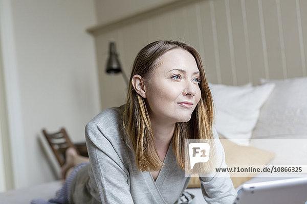Porträt einer Frau  die vorne auf dem Bett liegt und lächelnd wegschaut