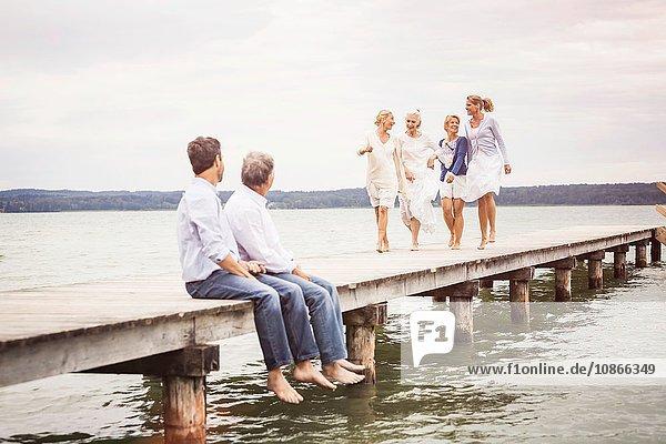 Gruppe von Freunden am Pier  weibliche Freunde gehen auf männliche Freunde zu  die am Rand des Piers sitzen