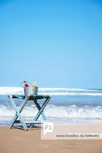Glasflaschen mit Saft im Eiskübel auf Liegestuhl am Strand