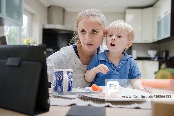 Mutter und Sohn sitzen am Tisch und schauen auf das digitale Tablett