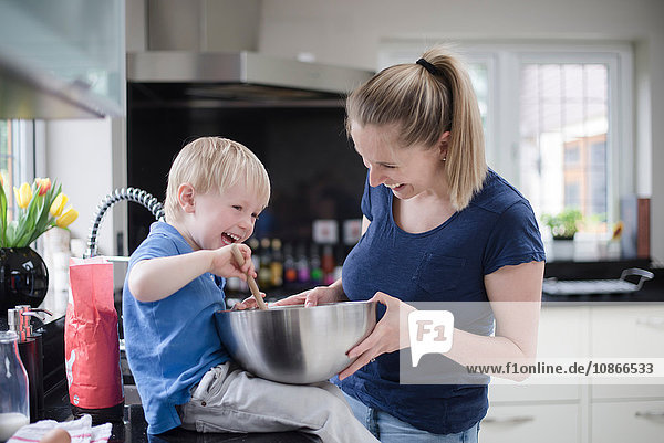 Mother and son fooling around whilst baking  stirring mixture in mixing bowl