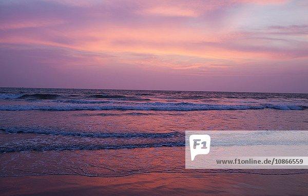 Sonnenuntergang über Wellen am Strand