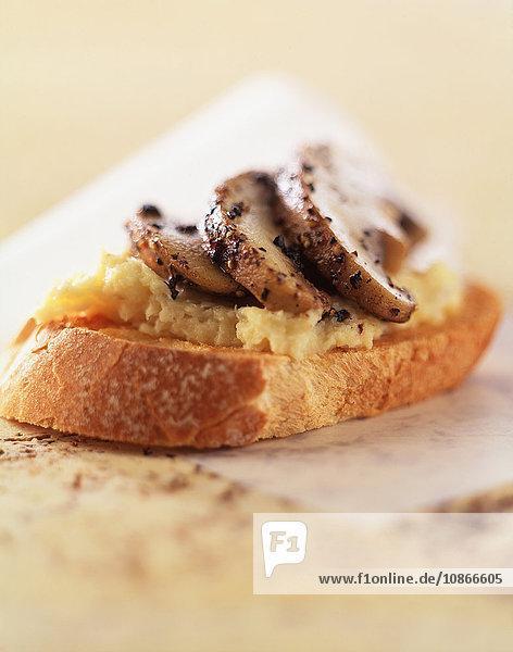 Pilze und Rührei auf knuspriger Baguettescheibe  Nahaufnahme