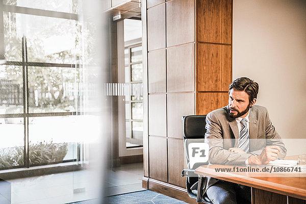 Geschäftsmann sitzt am Schreibtisch und schaut weg