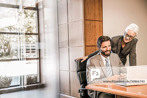 Businesspeople at desk looking at laptop smiling