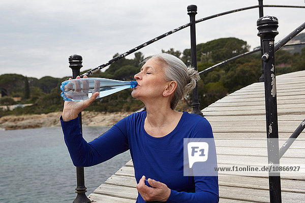 Mature woman outdoors  drinking from water bottle