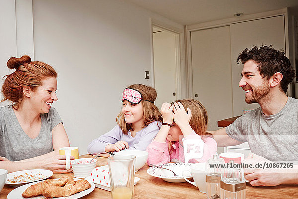 Mid adult parents at breakfast table with two daughters