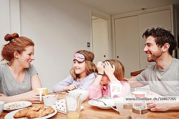 Mittlere erwachsene Eltern am Frühstückstisch mit zwei Töchtern