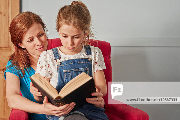 Mid adult woman reading book with daughter on armchair