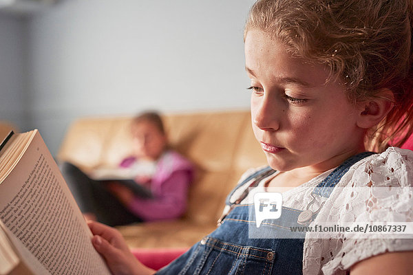 Close up of girl and her sister reading books in living room