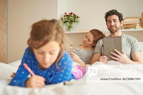 Mittelgroßes erwachsenes Paar  das im Bett liegt  während die Tochter im Bett zeichnet