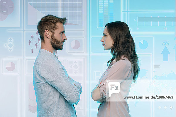 Man and woman standing face to face  data on graphical screen behind them