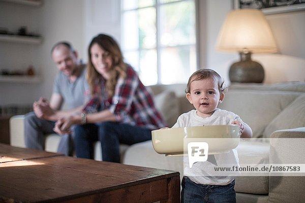 Kleiner Junge im Wohnzimmer hält große Schüssel und schaut lächelnd in die Kamera