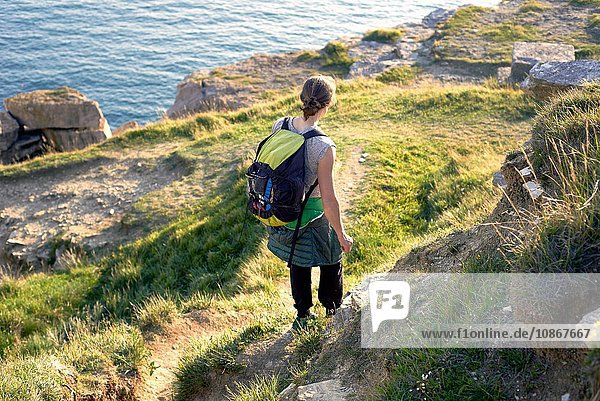 Hochwinkel-Rückansicht eines Wanderers mit Rucksack beim Wandern am Klippenrand  Portland  UK