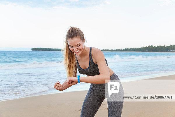 Junge weibliche Läuferin kontrolliert die Zeit am Strand  Dominikanische Republik  Karibik