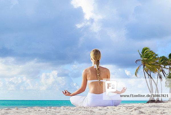 Rückansicht einer jungen Frau  die am Strand Lotus-Pose übt  Dominikanische Republik  Karibik