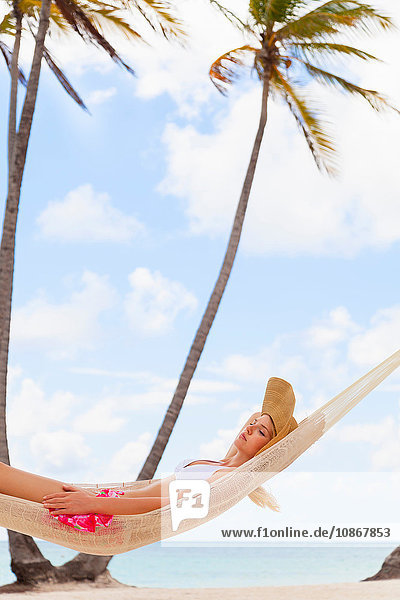 Junge Frau im Bikini zum Sonnenbaden in Strandhängematte  Dominikanische Republik  Karibik