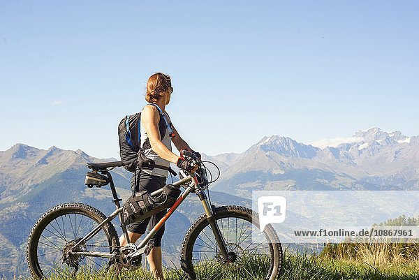 Female mountain biker looking out at mountain landscape  Aosta Valley  Aosta  Italy