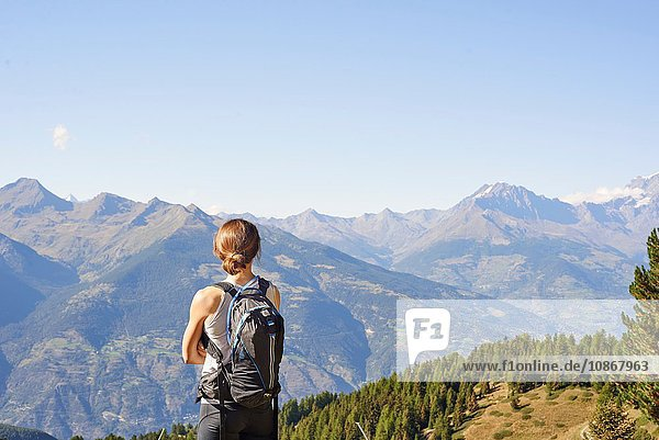 Rear view of female hiker looking out over mountain landscape  Aosta Valley  Aosta  Italy